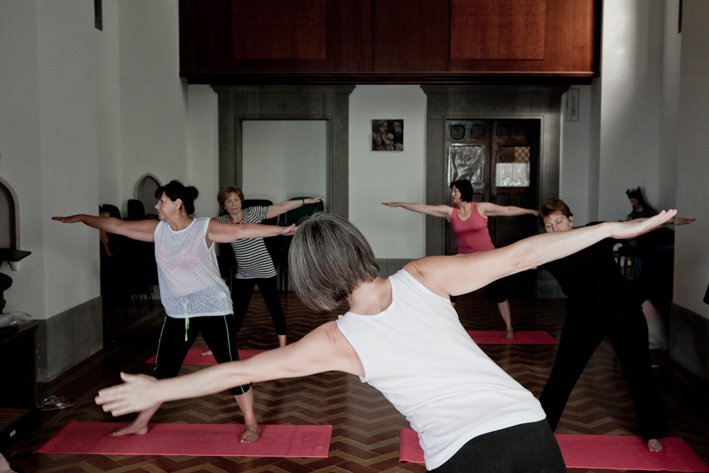 Rose and the class during an early morining indoor yoga session, Italy