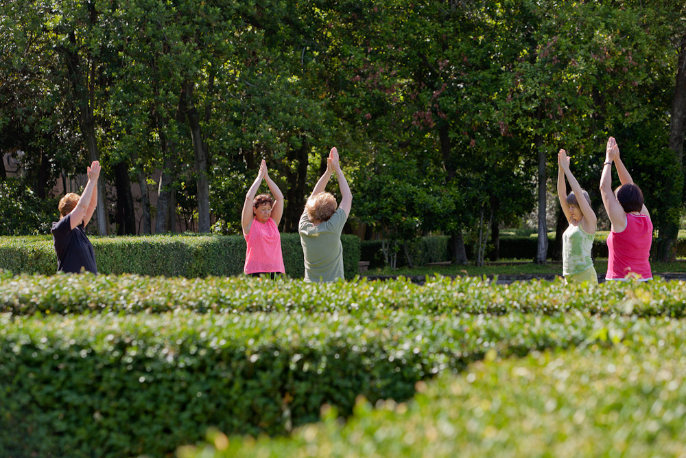 Rose and the class during an outdoor yoga session in the afternoon sunshine, Italy